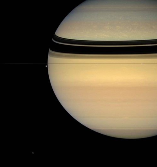 Image captured July 24, 2007. Saturn's rings are barely visible edge-on as they cast a shadow on the planet. Moons Tethys and Enceladus look tiny in comparison in line with the rings, as Hyperion sits bottom left.